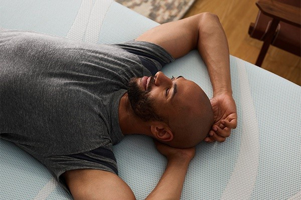 A man lying on a Tempur-Pedic mattress and adjustable power base system enjoying the 4 zone massage feature