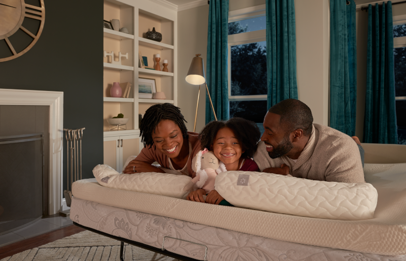 Family of three lying on mattress topper on couch pull out mattress with two Cloud pillows