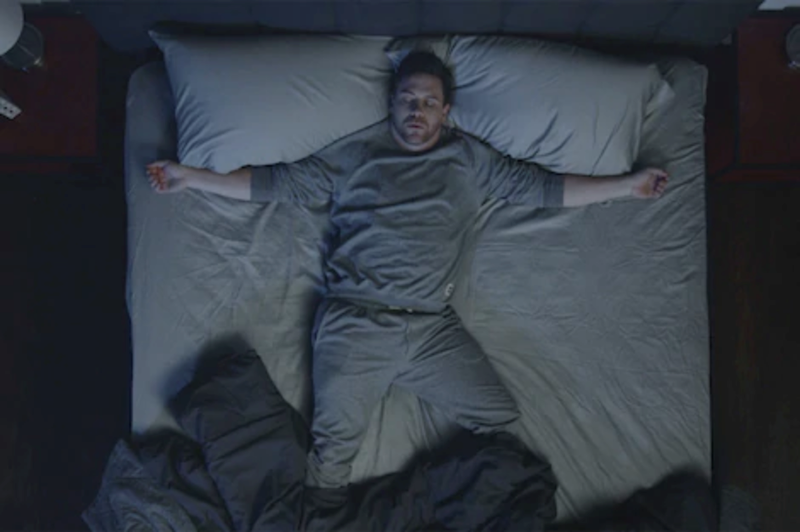 a man in bed, covers thrown off from sleeping hot