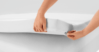 The corner of a mattress topper held up to show zipped cover