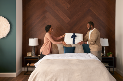 Woman handing cloud pillow to man standing by a bed.png