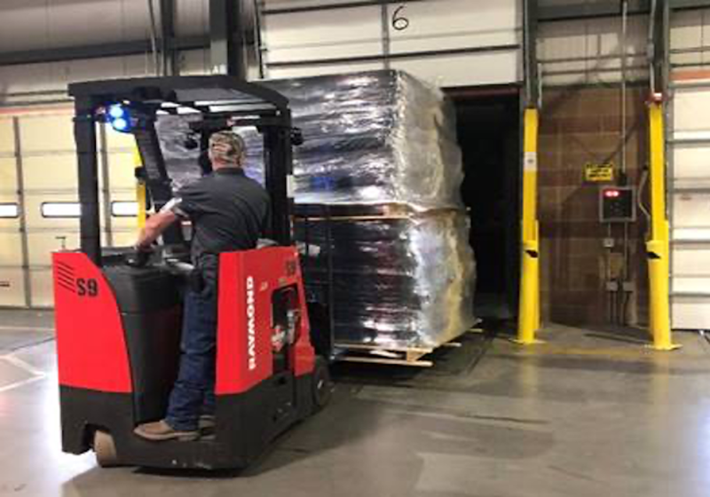 man on a forklift lifting mattresses.png